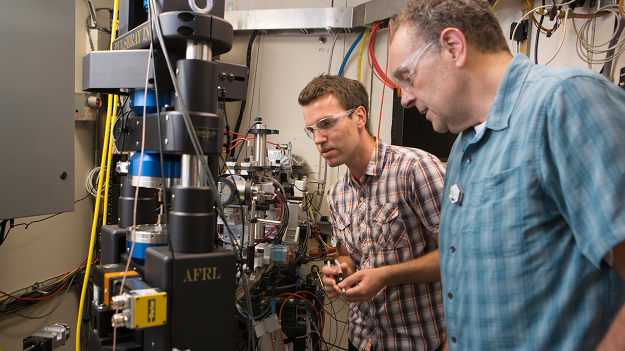 Graduate student Mark Obstalecki, left, prepares a sample for the Rotational and Axial Motion System (RAMS) in the F2 hutch at CHESS under the watchful eye of Matthew Miller, professor of mechanical and aerospace engineering and director of InSitµ@CHESS
